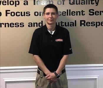 SERVPRO Employee Standing in front of a wall