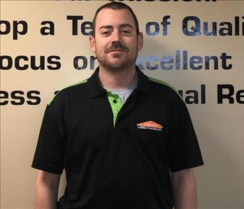 Male SERVPRO Employee Standing in front of wall